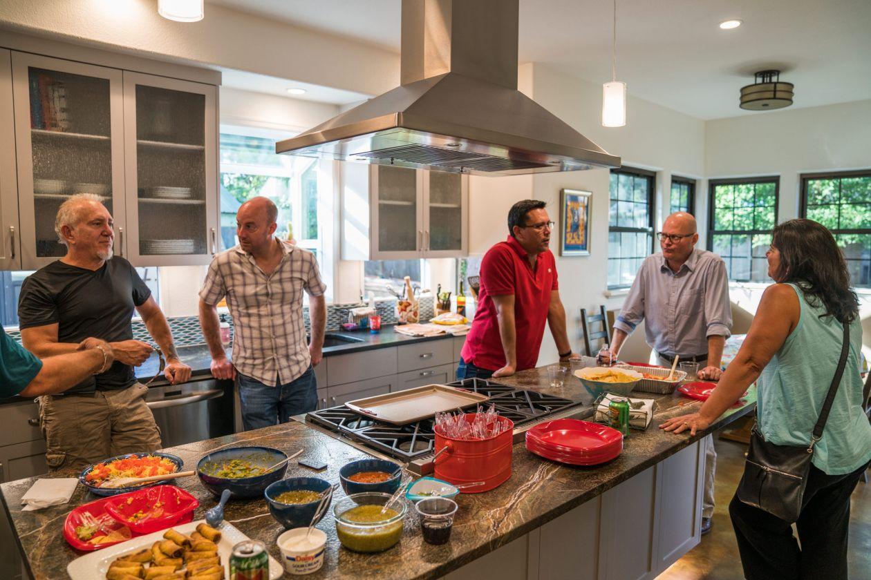 People Conversing Around Home Kitchen Island